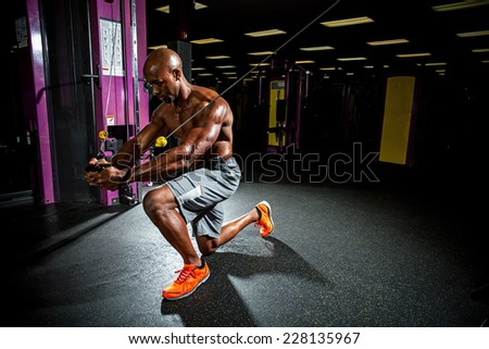 Muscular body builder working out at the gym doing chest fly exercises on the wire cable machine.