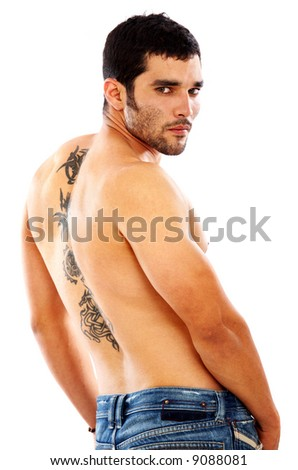 muscular fashion man showing his tatoo on his back and wearing jeans