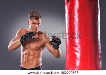 Muscular Fighter Prepare for Practicing Some Kicks with Punching Bag. Boxing on Gray Background. The Concept of a Healthy Lifestyle