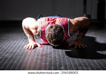 Muscular man doing push-ups in crossfit gym