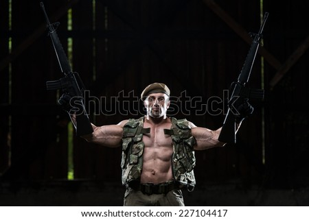 Muscular Man Holding Machine Guns - Standing In Abandoned Building Wearing Green Pants