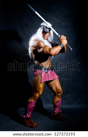 Muscular man in an image of a barbarian with a raised sword. On a dark background in full length