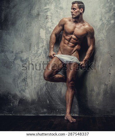 Muscular man in white panties posing in studio.