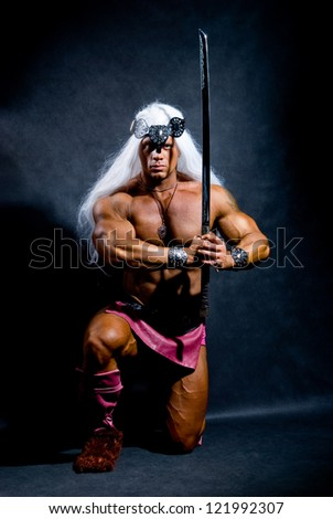 Muscular man with a sword and long white hair. The image of the warrior. black background