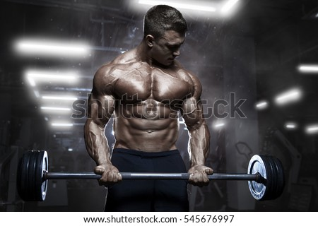Muscular man workout with barbell at gym. Brutal bodybuilder athletic man with perfect abs, shoulders, biceps, triceps and chest. Dead lift barbells workout
