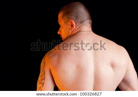 Muscular shirtless male standing with his back to the camera