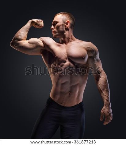 Muscular shirtless man in studio over dark background show his muscle.