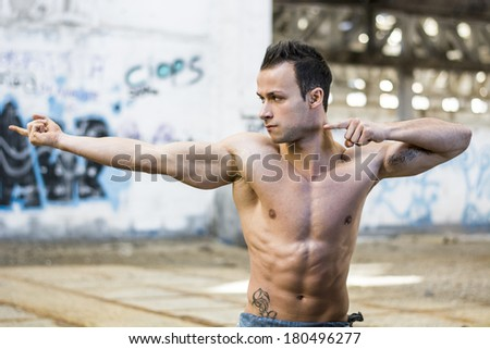 Muscular shirtless young man in abandoned warehouse standing, pointing with fingers to a side