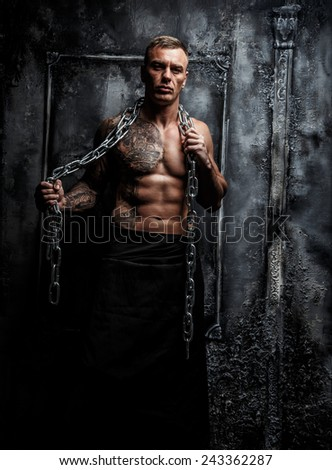 Muscular strong male with tattoo poses holding steel chain