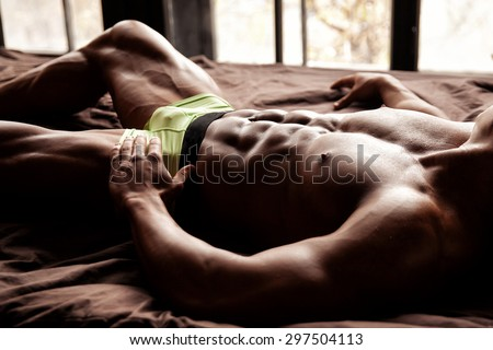 Muscular young sexy guy lies on the bed without clothes in underwear