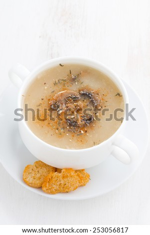 mushroom cream soup with croutons on white wooden table, vertical, top view