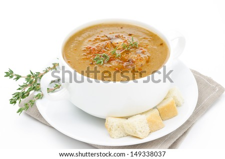 Mushroom soup in a bowl with croutons and thyme isolated on white background