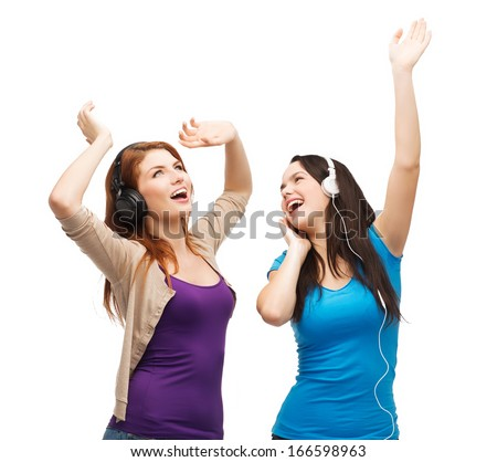 music and technology concept - two laughing teenagers with headphones dancing