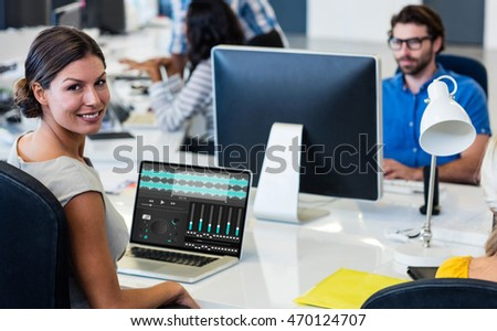 Music app against portrait of woman with colleagues working
