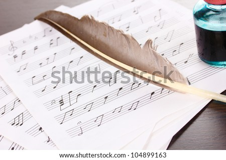Musical notes and feather on wooden table