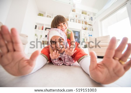 Muslim traditional mother with little cute son at home in living room