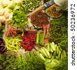 Muslim woman selling fresh vegetables at market in Kota Bharu Malaysia - stock photo