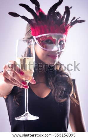 Mysterious woman wearing a red mask, holding a glass of champagne at a masquerade party celebration new years eve party