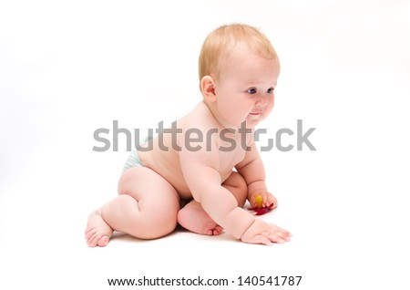 Naked baby crawling on the floor intently with red pacifier in his hands