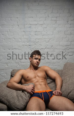 Naked man on sofa on white wall background