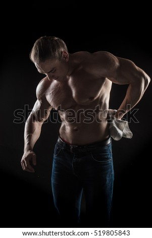 naked torso male bodybuilder athlete with a towel on a black background