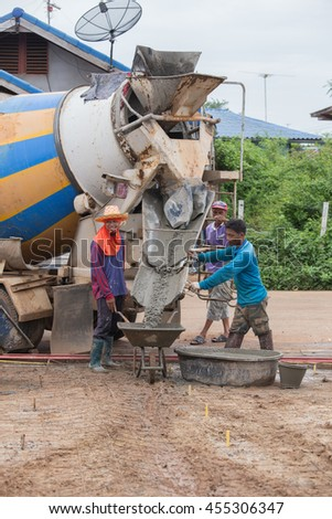 NAKHON RATCHASIMA -JULY 6 : A cement truck is pouring cement to cart at consrtuction site on July 6, 2016 in Nakhon Ratchasima, Thailand