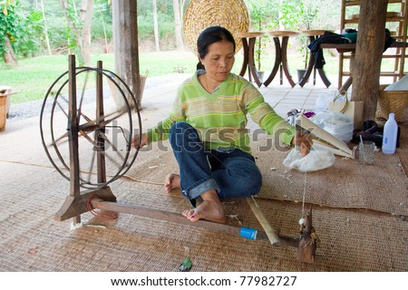NAKHON-RATCHASIMA, THAILAND - DECEMBER 25: Traditional old style for pulling out silk thread from the cocoon and spining them to keep on spool on December 25, 2008 in Nakhon-Ratchasima, Thailand.