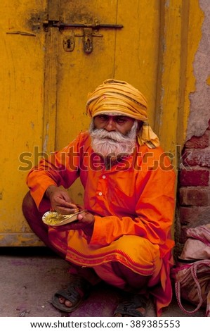 NANDGAON - MARCH 22 : Unidentified hindu sadhu with face smeared with colors participate in the colorful Holi celebration at Krishna temple on March 22, 2013 in Nandgaon, Uttar Pradesh, India.