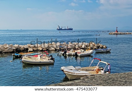 NAPLES, CAMPANIA, ITALY - AUGUST 5, 2016: Beautiful summer panoramic seascape from Naples waterfront including cargo ship, small motorboats and lighthouse in the Tyrrhenian Sea, Naples, Italy