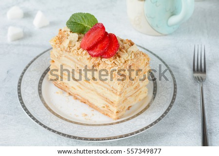 Napoleon cake, layered cake with pastry cream, custard decorated with strawberries and mint. Close up view. Piece of homemade cake
