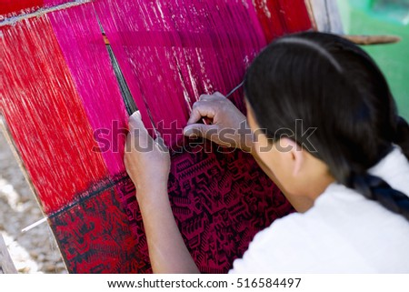 Native Peruvian woman weaving intricate llama wool garments using a traditional hand loom