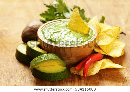Natural fresh guacamole dip with avocado and corn chips.