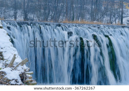 Natural frozen water cascade in cold mountain river
