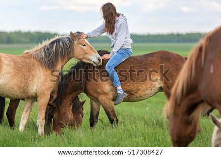 Natural horsemanship of a young woman and a herd of horses.