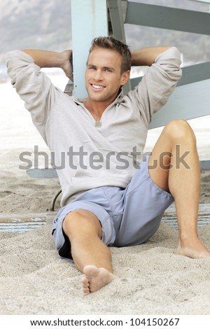 Natural outdoor portrait of great looking young man with big smile leaning in sand