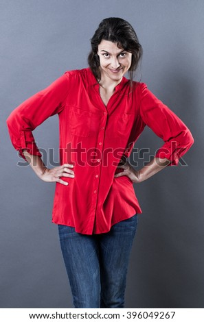 natural smile - proud young woman standing with hands on hips expressing happy self-confidence, contrast effects.