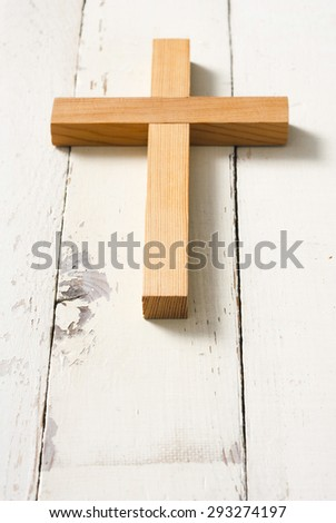 natural wooden cross on aged bright wood table background