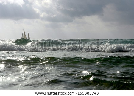 nature, seascape, rough sea, a lone sailboat on the crest of a wave