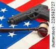 Neat judge gavel and gun over USA flag - studio shoot - stock