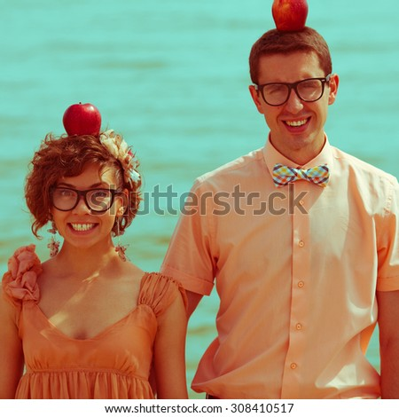 Nerds' honeymoon concept. Portrait of couple of young happy married hipsters in trendy vintage clothes standing together on the beach with apples on their heads. Sunny summer day. Outdoor shot