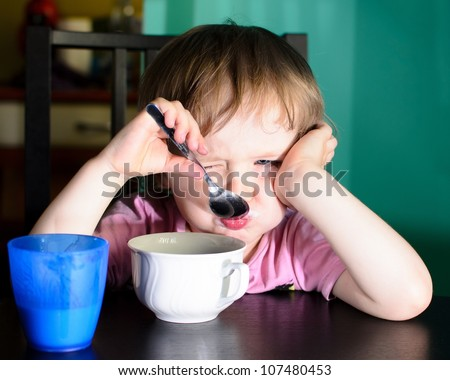 Nervous little boy eating and drinking milk