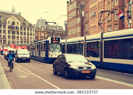 NETHERLANDS. AMSTERDAM - JUNE 23, 2015: Public transport in the city street against the backdrop of historic architecture.
