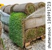 New green turf grass rolls stacked in a pile on wooden pallets ready to be used in a city, park, stadium, sport arena or in a formal garden - stock photo