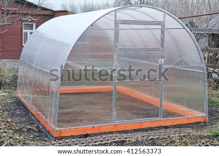 New greenhouse made of transparent polycarbonate in the yard