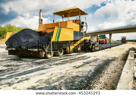 New Road - Pavement machine laying fresh asphalt or bitumen on top of the gravel base during highway construction