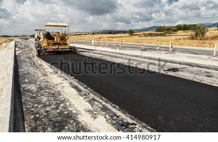 New Road -Pavement machine laying fresh asphalt or bitumen on top of the gravel base during highway construction