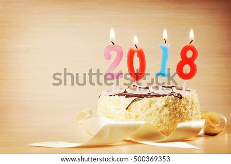 New Year 2018 composition. Cake and burning candles against brown background