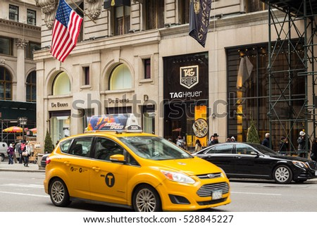 NEW YORK CITY - MARCH 14, 2014:  View along fashionable Fifth Avenue in Manhattan with yellow taxi cab, people and Tag Heuer store in view.