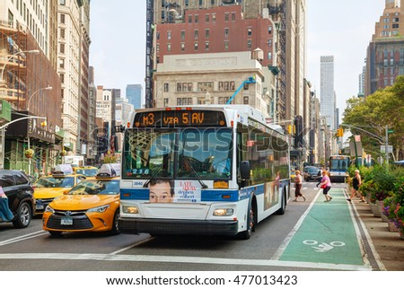 NEW YORK CITY - SEPTEMBER 04: Yellow cab and bus with people at 5th Avenue on September 4, 2015 in New York City. It's the most populous city in the US and the center of the New York metropolitan area