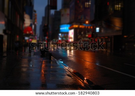 New York City street after rain with reflections on wet surface of asphalt at night blurred view. Colorized image. Blurred city for background usage vintage tone.